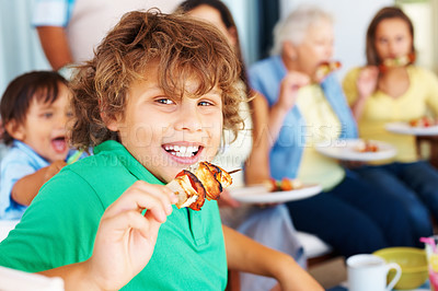 Buy stock photo Little boy eats shish kebab from skewer with family in the background
