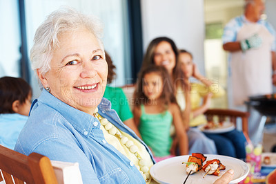 Buy stock photo A happy senior woman having shish kebab with her family in the background