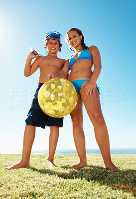 Buy stock photo Low angle view of brother and sister in a swimming costume standing together