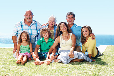 Buy stock photo Full length portrait of three generation family relaxing on grass