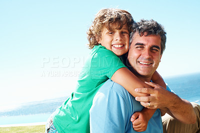 Buy stock photo Smiling little boy embracing his father from behind outdoors