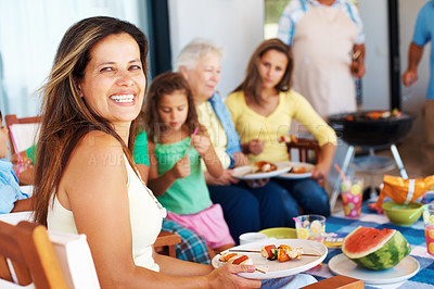 Buy stock photo Happy mature woman smiling at you while enjoying a barbecue with family and friends - copyspace