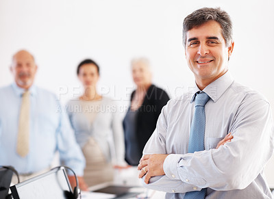 Buy stock photo Smiling business man with hands folded and colleagues in background