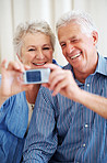 Happy senior couple taking a self portrait on mobile phone