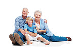 Happy senior couple sitting relax on floor with a little boy