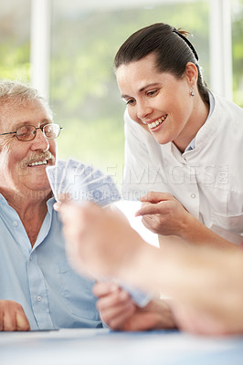 Smiling lady helping a senior man in playing game of card