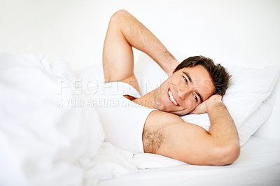 Happy young man waking up in morning on bed
