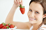 Closeup of a smiling female holding a plate of strawberries