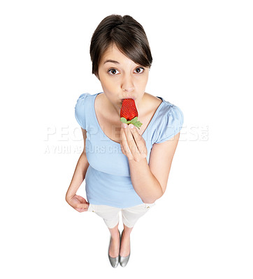 Buy stock photo Top view portrait of a cute female eating a fresh strawberry against white