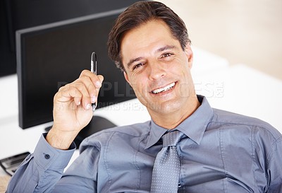 Buy stock photo Portrait of a  happy mature businessman sitting at his desk holding a pen