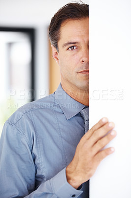 Buy stock photo Shy mature business man peeking behind a white wall