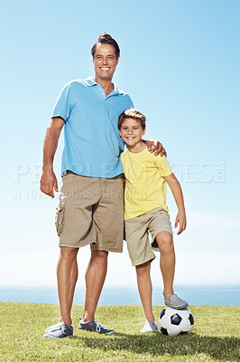 Buy stock photo Full length of happy man and his cute son with a football on grass field on a sunny day