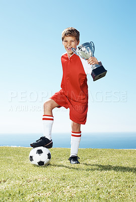 Buy stock photo Portrait of an excited small football player showing winners trophy - Outdoors on field