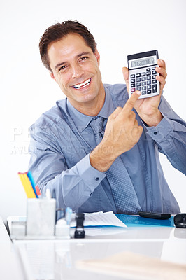 Buy stock photo Portrait of happy businessman sitting at his office desk and pointing at a calculator in hand