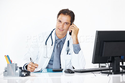 Buy stock photo Portrait of handsome male doctor working at desk in office talking on mobile phone