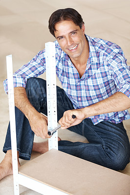 Buy stock photo Craftsman tightning a bolt in a metal rack in his workshop