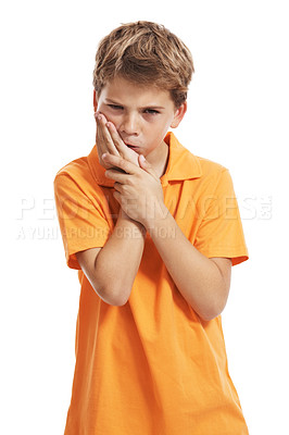 Buy stock photo Young boy standing with his hand on his mouth suffering from a sore tooth isolated against white backround