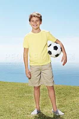 Buy stock photo Portrait of a young cute happy boy holding a soccer ball outside