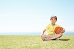 Cute little boy sitting on grass with a basketball - Copyspace