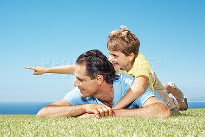 Buy stock photo Portrait of a small boy lying on back of his father om grass and pointing away at copyspace
