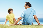 Happy man and his son sitting relax on grass