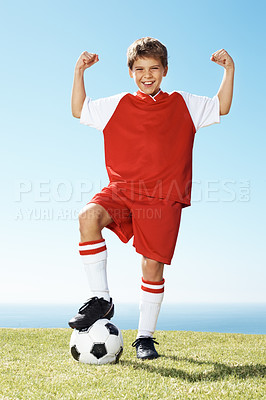 Buy stock photo Portrait of a happy little boy standing with soccer ball under his feet showing his muscles