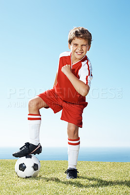 Buy stock photo Portrait of an exited little boy with soccer ball under his feet on ground
