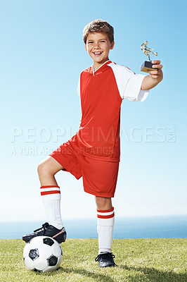 Buy stock photo Portrait of an excited small boy with a football showing a winners trophy at ground