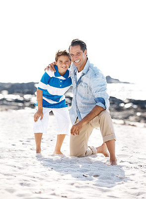 Buy stock photo Portrait of a happy little boy and his father standing with arms around at the beach