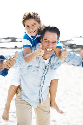 Buy stock photo Portrait of a smiling mature father giving his son piggyback ride on the beach with thumbs up