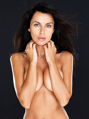 Buy stock photo Portrait of a nude young girl standing with hands covering her breast against dark background