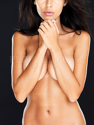Buy stock photo Closeup of nude young female covering her breast with her hands against black background