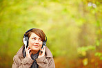 Woman listening to music outside in the forest