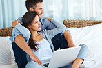 Relaxed couple with laptop at home