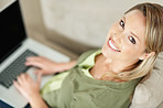 Smiling relaxed young female using a laptop at home