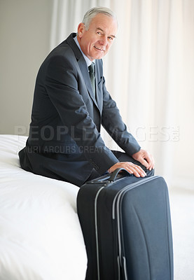 Happy senior man sitting on bed with his luggage