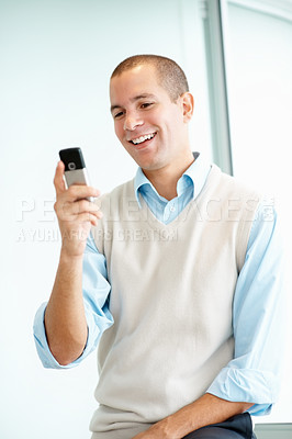 A happy young man reading a text message