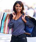 Happy young woman standing with shopping bags