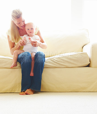 Mother with her baby boy sitting on sofa at home