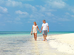 Relaxed mature couple strolling by the sea shore