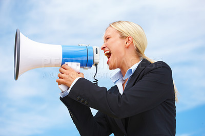 Business woman shouting through megaphone