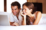 Young couple lying on bed with laptop smiling