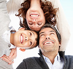 Closeup of happy mature parents with son huddling against white