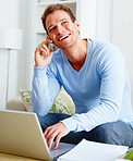 Laughing man using a computer laptop and mobile phone