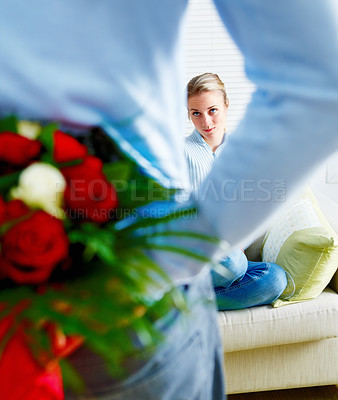 Buy stock photo Young man hiding flowers before a beautiful smiling woman