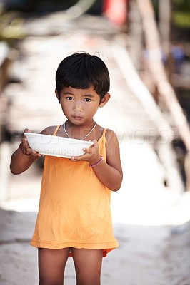 Buy stock photo Portrait of a young kid from rural Thailand holding a bowl of food and looking