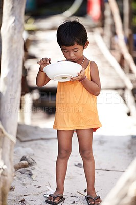 Buy stock photo Portrait of a young kid from rural Thailand eating food while standing