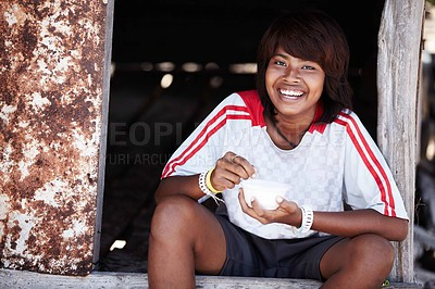 Buy stock photo Portrait of a happy teenager from rural thailand eating her meal