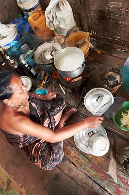 Buy stock photo A Thai woman sitting on the floor making food