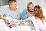 Modern family enjoying their breakfast on the bed